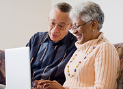 An elderly couple sit on a couch, looking at a computer