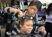 A woman cuts another woman's hair
